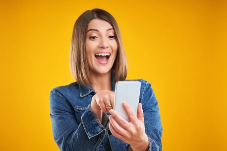 Close up of woman in denim jacket with smartphone over yellow background