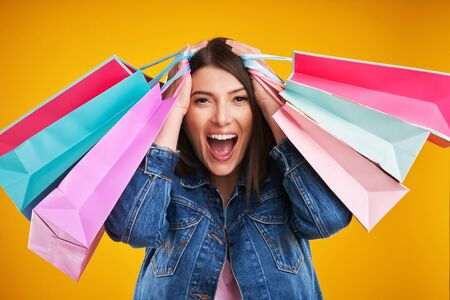 Close up of woman in denim jacket with shopping bags over yellow background