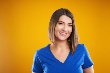 Close up of woman in blue t-shirt looking at camera over yellow background Stockfoto
