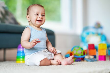 Cute smiling baby boy sitting on floor in living room Stockfoto