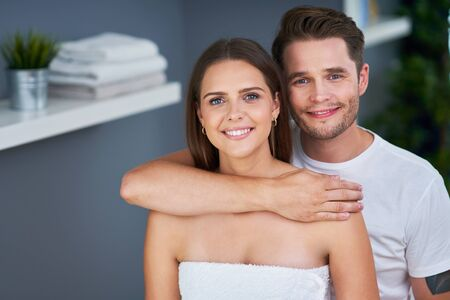 Portrait of happy young couple cuddling in the bathroom