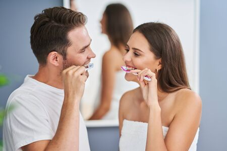 Portrait of happy young couple brushing teeth in the bathroom Stockfoto