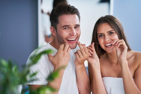 Portrait of happy young couple flossing teeth in the bathroom