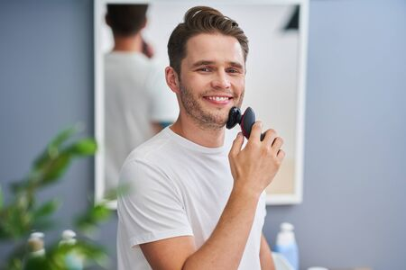 Portrait of adult man shaving in the bathroom Stockfoto
