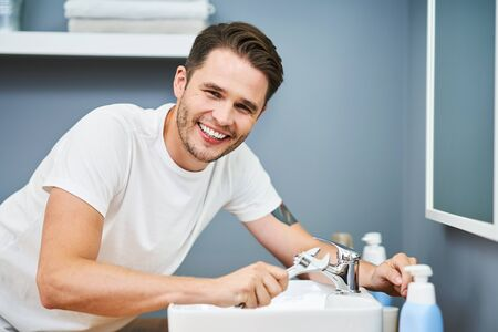 Portrait of adult man fixing sink in the bathroom