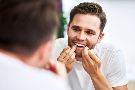 Adult man flossing teeth in the bathroom Stockfoto