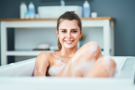Young woman enjoying and relaxing in the bathtub