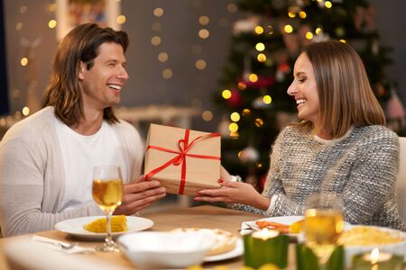Beautiful couple sharing presents during Christmas dinner Archivio Fotografico - 129606435