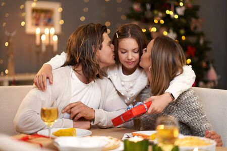 Beautiful family with presents sharing presents during Christmas dinner Archivio Fotografico - 129606438