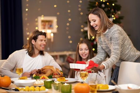 Beautiful family eating Christmas dinner at home Archivio Fotografico - 129606439