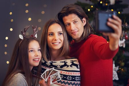 Beautiful family celebrating Christmas at home and taking instant pictures Archivio Fotografico - 129606440