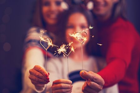 Beautiful family celebrating Christmas and holding sparklers Archivio Fotografico - 129606473