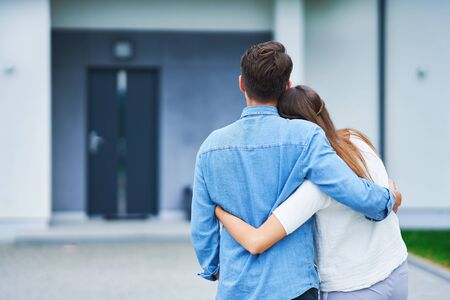 Couple in front of one-family house in modern residential area Stock fotó