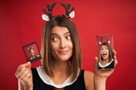 Woman in Christmas mood comparing instant pictures to smartphone camera over red