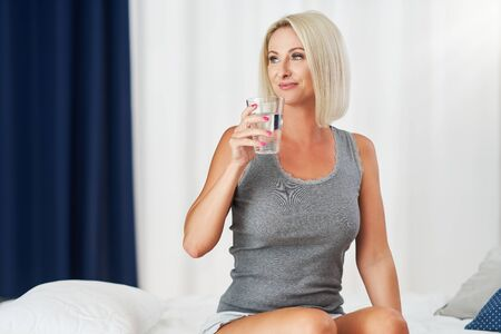 Adult beautiful woman waking up fully rested and drinking water