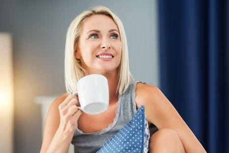 Adult beautiful woman waking up fully restedand drinking coffee Фото со стока