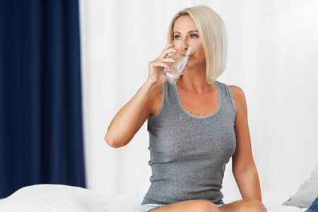 Adult beautiful woman waking up fully rested and drinking water Фото со стока - 130840993