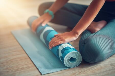 Young woman rolling yoga mat at home Stock Photo