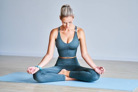 Adult woman practising yoga at home Stock Photo