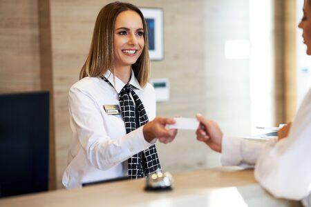 Réceptionniste donnant une carte-clé à une femme d'affaires à la réception de l'hôtel
