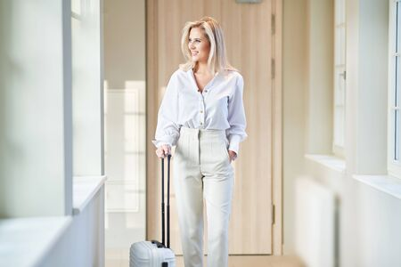 Businesswoman with luggage in modern hotel lobby