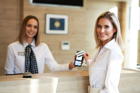Receptionist and businesswoman at hotel front desk Reklamní fotografie