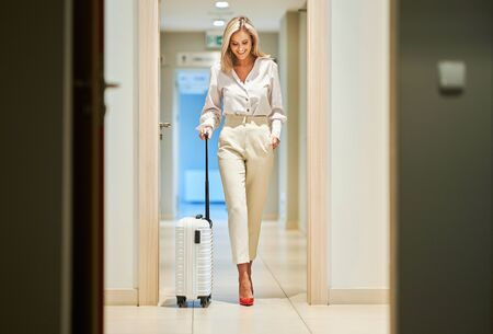 Businesswoman with luggage in modern hotel lobby Reklamní fotografie