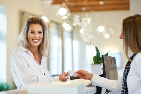 Receptionist and businesswoman at hotel front desk 版權商用圖片