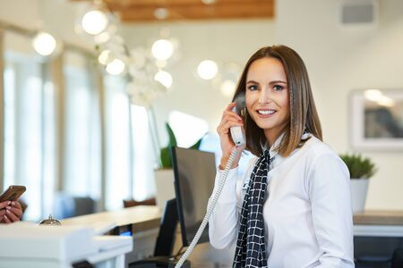 Réceptionniste répondant au téléphone à la réception de l'hôtel
