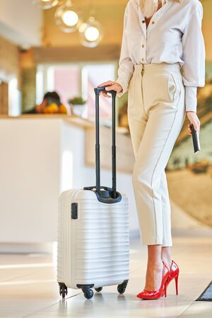 Businesswoman with luggage in modern hotel lobby using smartphone 版權商用圖片