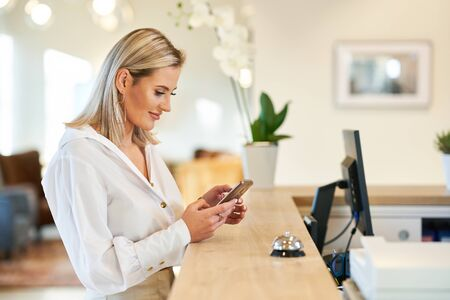 Businesswoman using smartphone at hotel front desk