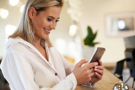 Geschäftsfrau mit Smartphone an der Hotelrezeption