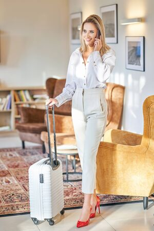 Businesswoman with luggage in modern hotel lobby using smartphone 스톡 콘텐츠