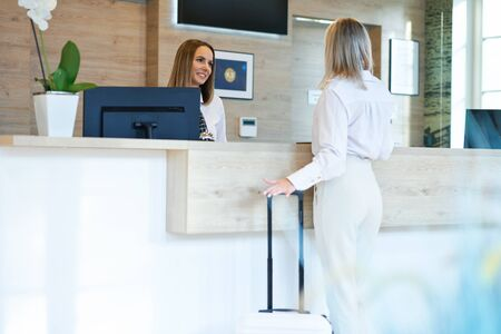 Receptionist and businesswoman at hotel front desk 스톡 콘텐츠