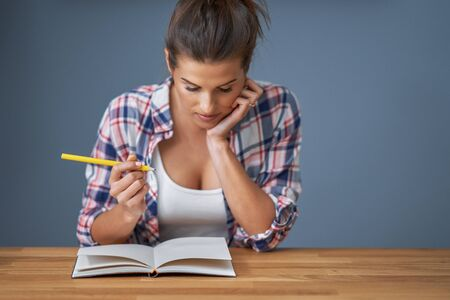 Tired female student learning till late at home