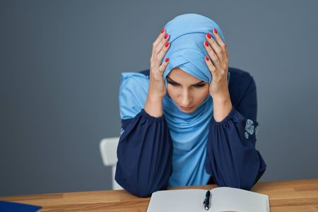Unhappy muslim female student learning at home Banco de Imagens