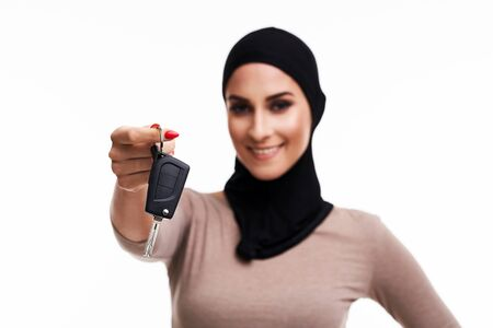 Muslim woman with car keys over white background Banco de Imagens