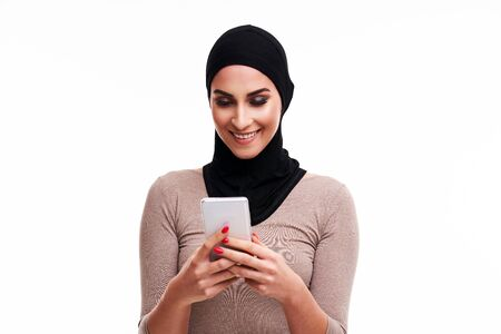 Muslim woman using smartphone over white background