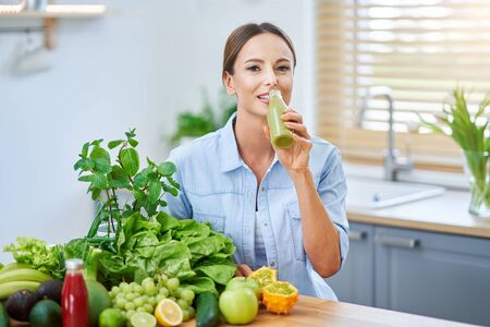 Healthy adult woman with green food in the kitchen Zdjęcie Seryjne