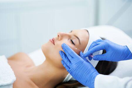 Beautiful young woman getting polydioxanone thread lifting at beauty salon.