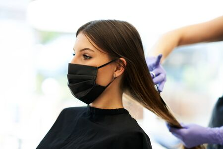 Adult woman at hairdresser wearing protective mask due to coronavirus pandemic Banque d'images