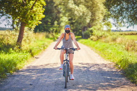 Young woman on a bike in countryside wearing a mask Фото со стока