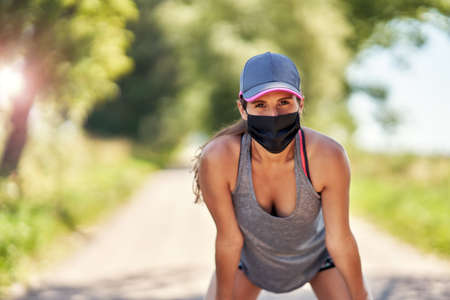 Female jogger running in mask in the countryside