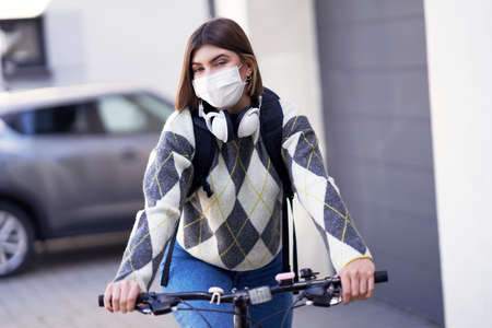 Teenager going to school by boke with a mask on