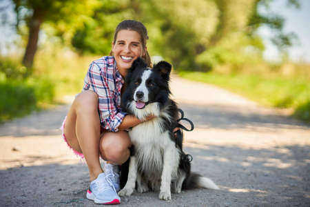 Portrait of happy female strolling with her pet at leisure