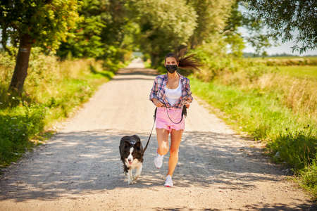 Picture of adult woman strolling with her pet and wearing a mask Фото со стока
