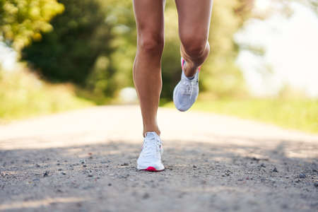 Down section of female runner jogging in the countryside