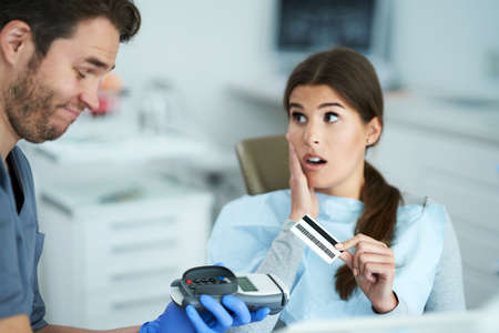 Dissatisfied woman paying for visit in dentist office