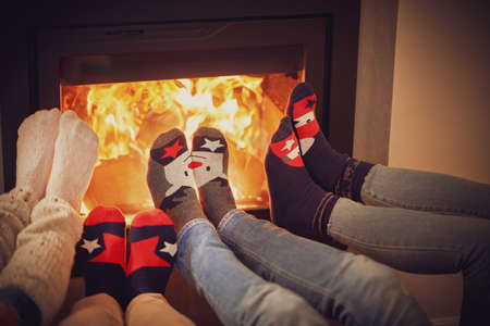Legs of group of friends relaxing over the firepllace Stock Photo