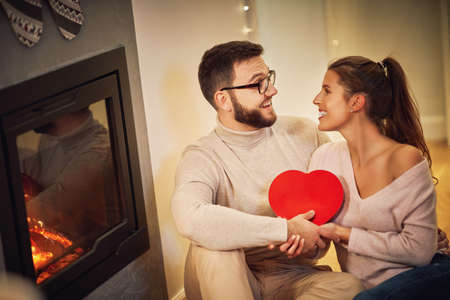 Adult couple with present over fireplace Archivio Fotografico